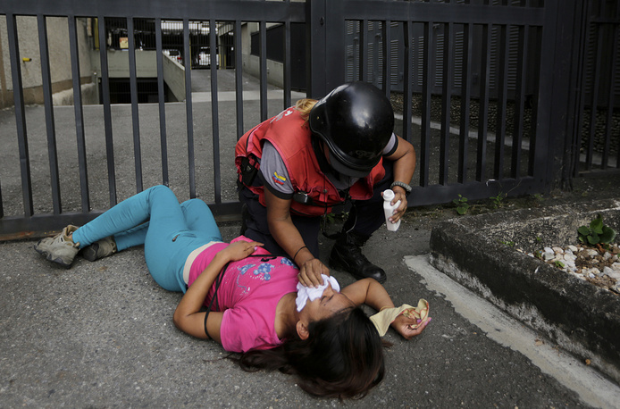 An anti-government protester who was overcome by tear gas is aided by a paramedic during clashes in Caracas