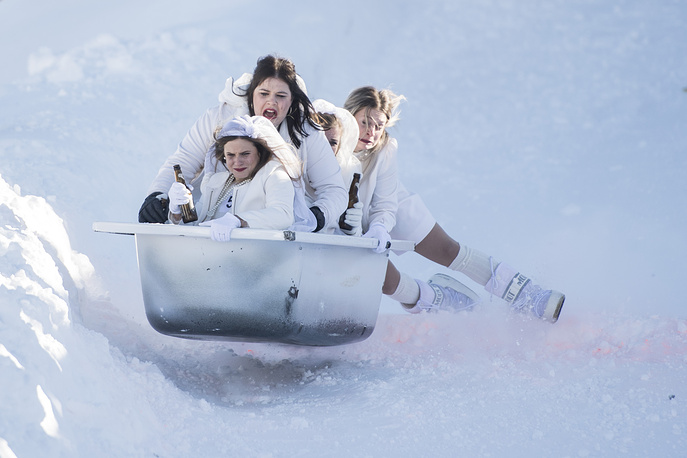 People in funny costumes race down the slope in bathtubs during the 7th Bathtub race at Stoos, January 19