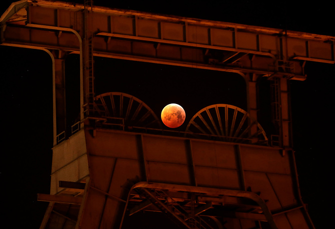 A view of the so-called blood moon next to the mine winding tower of Ewald colliery during the first total lunar eclipse of the year in Herten, Germany, January 21