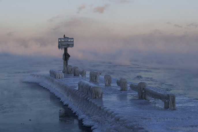 A harbor light is covered with snow and ice on the Lake Michigan