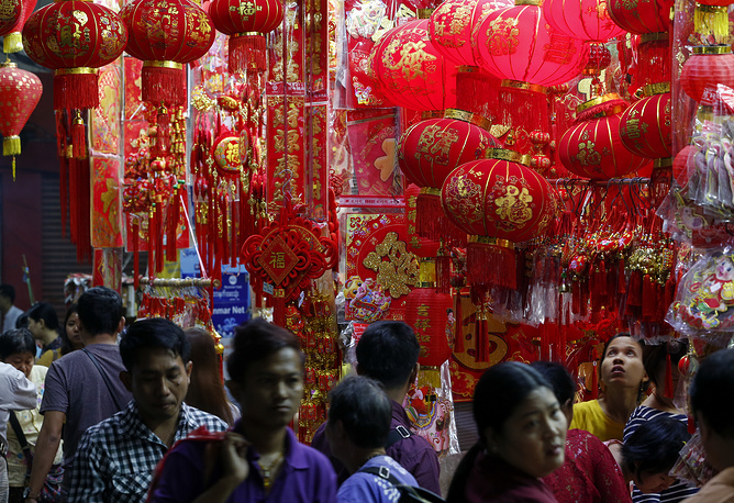 Pedestrians walk past a shop selling lanterns and Chinese traditional ornaments for the upcoming Lunar New Year or Spring Festival at Chinatown in Yangon, Myanmar