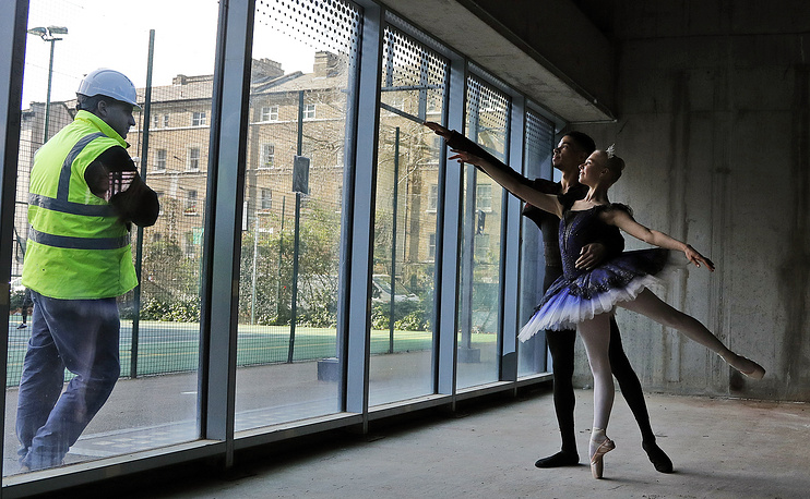 A worker watches as Ballet dancers pose for photos as building works commence at Central School of Ballet's new SE1 premises, London, February 20
