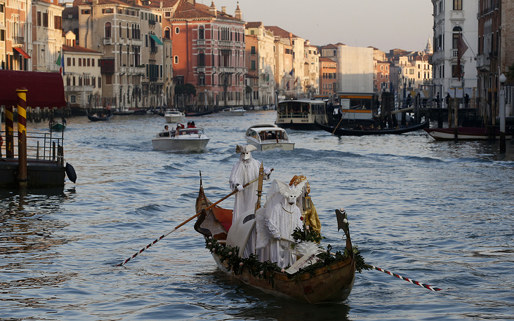 Masked people stand on a gondola as part of the Carnival in Venice, February 16