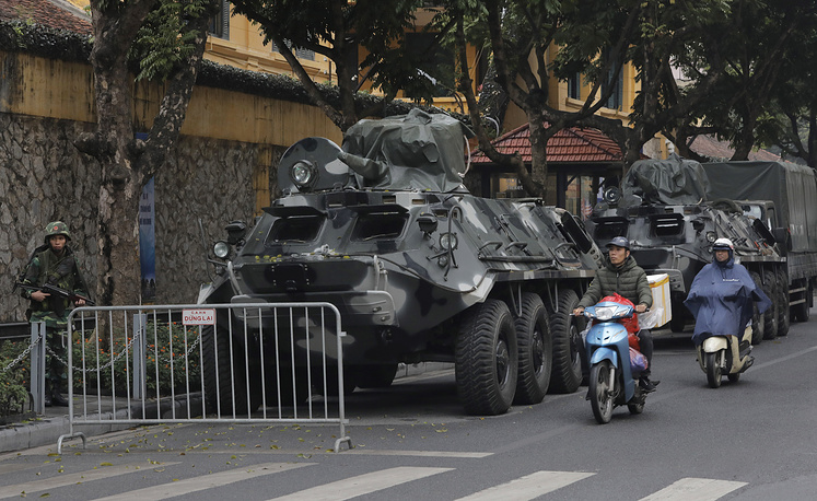 Motorists pass by army vehicles outside the Melia Hotel where North Korea leader Kim Jong Un is expected to stay at, in Hanoi
