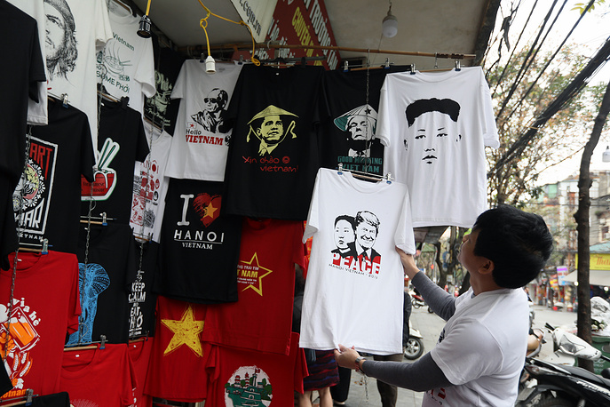 A visitor looks over a newly designed T-shirt decorated with the portraits of US President Donald Trump and North Korean leader Kim Jong-un at a sidewalk store in Hanoi