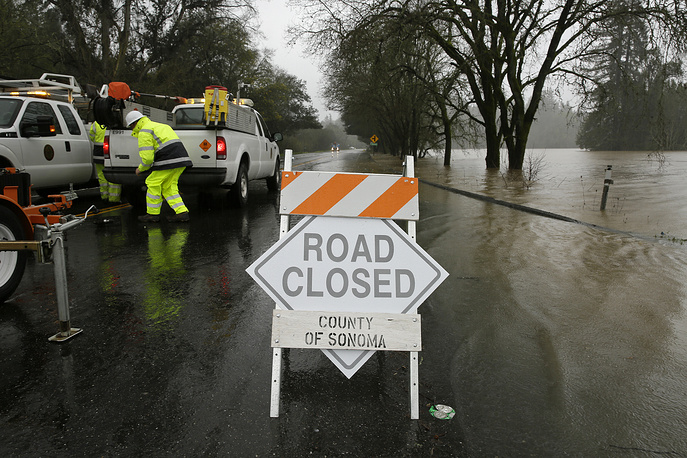 Rising flood water makes its way onto River Road in Forestville, California