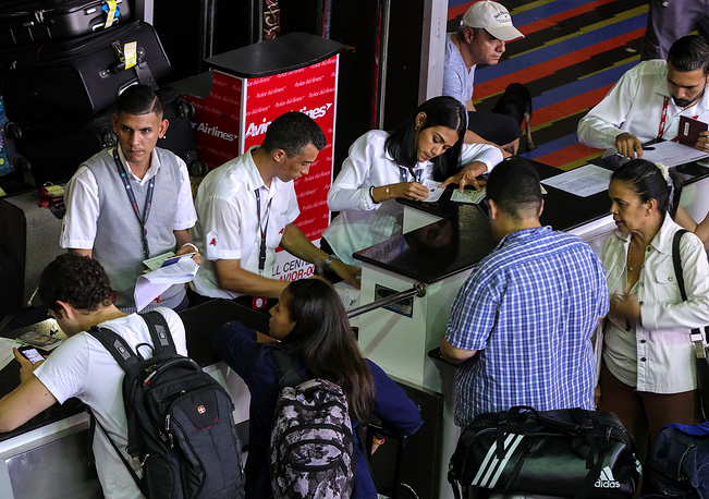 Passengers are seen at the Simon Bolívar International Airport as international flights are delayed due to power outage in Venezuela