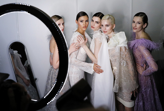 Models prepare to showcase creations during a runway show for a collection of Speranza Couture by Nadezhda Yusupova