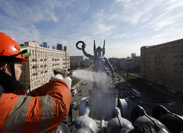 A municipal worker uses a high-pressure washer to clean an equestrian statue on top of the Triumphal Arch at Kutuzovsky Prospekt Street in Moscow, April 18