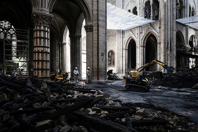 Workers standing near the rubble in the Notre Dame de Paris Cathedral during preliminary work one month after it sustained major fire damage