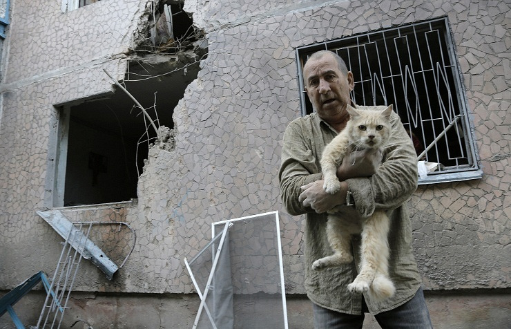 A man carries his injured cat in front of his damaged house after shelling in the city of Sloviansk AP Photo/Dmitry Lovetsky