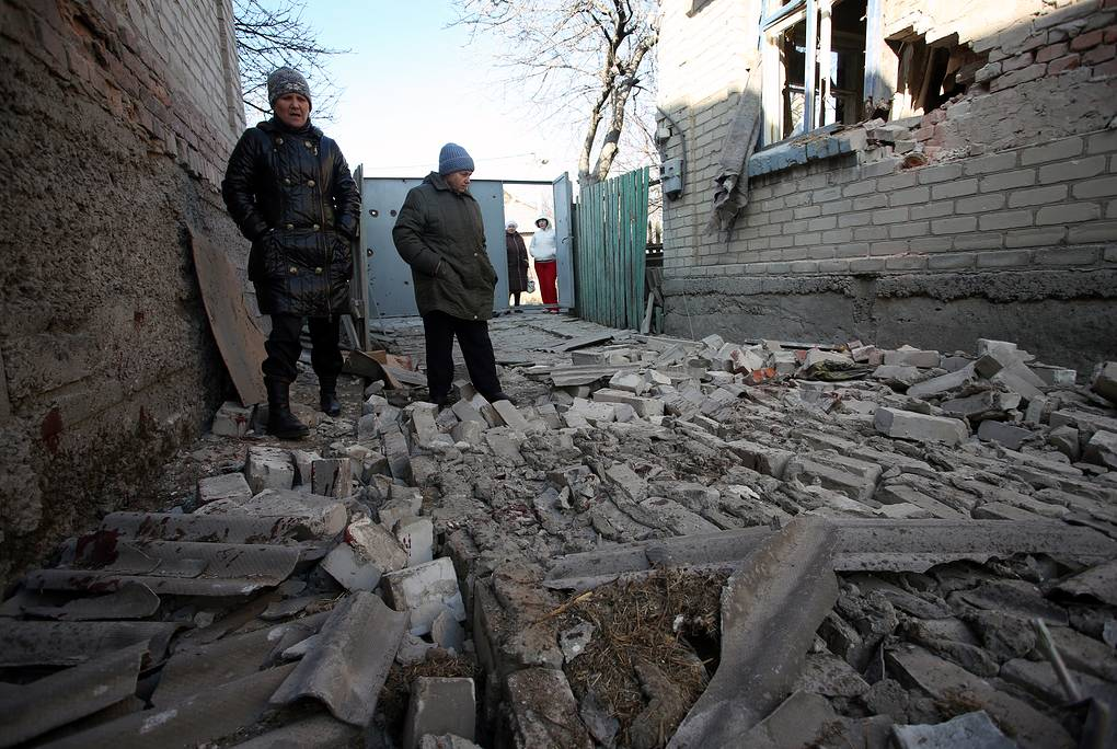Local residents seen by a house damaged in a shelling attack in Donetsk region Alexander Kravchenko/TASS