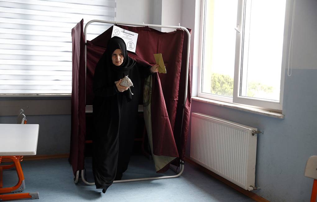 A woman leaves a voting booth at in Istanbul AP Photo/Lefteris Pitarakis