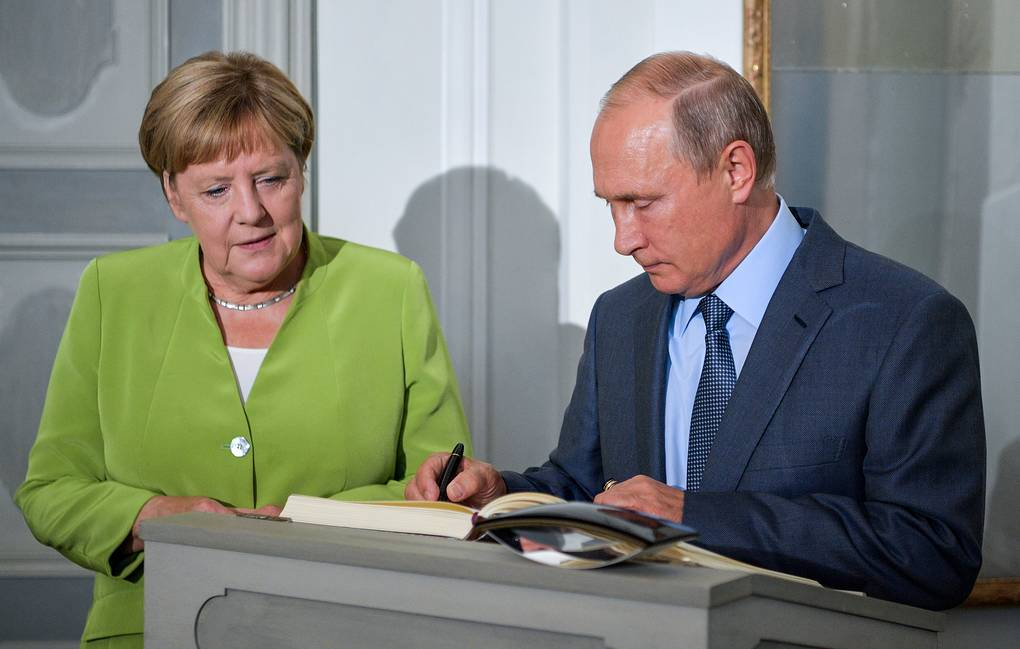 Russia's President Vladimir Putin signs a distinguished visitors' book as he meets with German Chancellor Angela Merkel Alexei Druzhinin/TASS