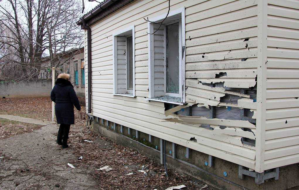 A woman standing next to her house in the village of Yelenovka, 20km southwest of Donetsk, shelled by the Ukrainian armed forces Valentin Sprinchak/TASS