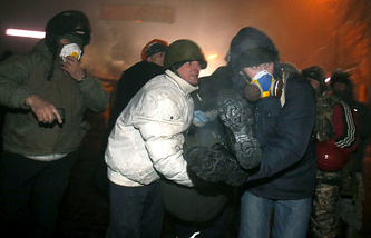 Protesters assist a wounded comrade, in central Kiev, Ukraine