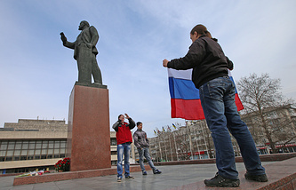 Citizens making photos with a Russian flag near a Lenin monument in Simferopol on Mar. 1, 2014