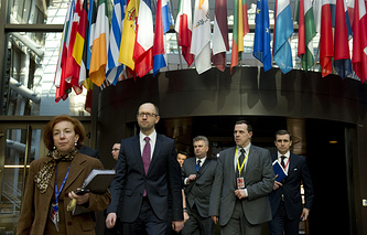 Arseniy Yatsenyuk, center left, as he walks to a media conference at an EU summit in Brussels