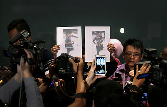 Journalists take pictures of the two men, a 19-year-old Iranian identified by Malaysian police as Pouria Nour Mohammad Mehrdad, left, and the man on the right, his identity still not released