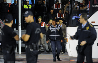 Police and paramilitary police officers escort Akin Celik, the mining company's operations manager, center-right