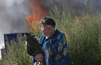 A woman cries near her burning house after shelling in east Ukraine's Donetsk Region, Jun. 30