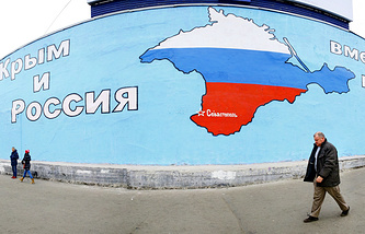 A man walks past a wall with contour of Crimean peninsula painted in the colors of Russia's national flag