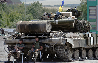 Ukrainian government army's soldiers rest near their tank