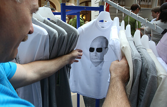 A man chooses a T-shirt with a p[ortrait of Vladimir Putin printed on it