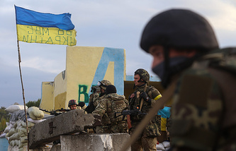 Ukrainian servicemen take up positions at a checkpoint during an exchange of Ukrainian troops and militia fighters near Slavianoserbsk, eastern Ukraine