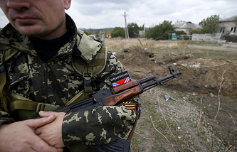 A militia fighter guards a mass grave found near Donetsk