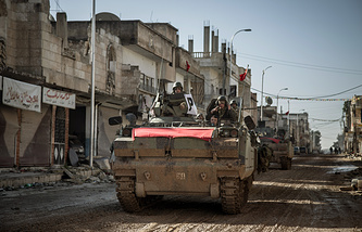 Turkish army's armored vehicles and tanks drive in Syrian town of Kobani, Feb 22, 2015