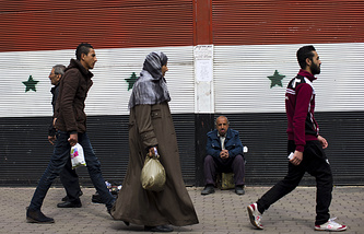 Syrians walking past a building with a painting of the national flag in Damascus