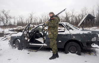 Ukrainian serviceman near a car, damaged after shelling during a patrol in Donetsk area