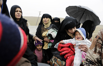 Families flee clashes between Iraqi forces and Islamic State group militants in Mosul