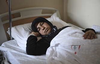 A Syrian woman rests in a hospital in Reyhanli, Turkey