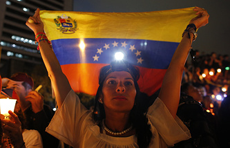 A demonstrator holds a Venezuelan flag in Caracas, Venezuela
