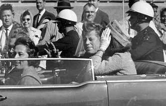John F. Kennedy waves from his car in a motorcade approximately one minute before he was shot in Dallas, Nov. 22, 1963