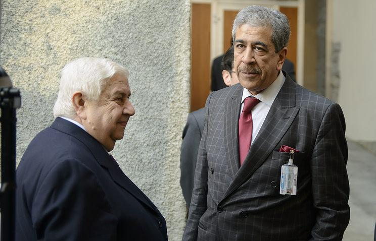 Syrian Foreign Minister Walid Muallem (L) stands next to Mukhtar Lamani (R), Head of the Office of the United Nations envoy to Syria, during a break of the so-called Geneva II peace talks