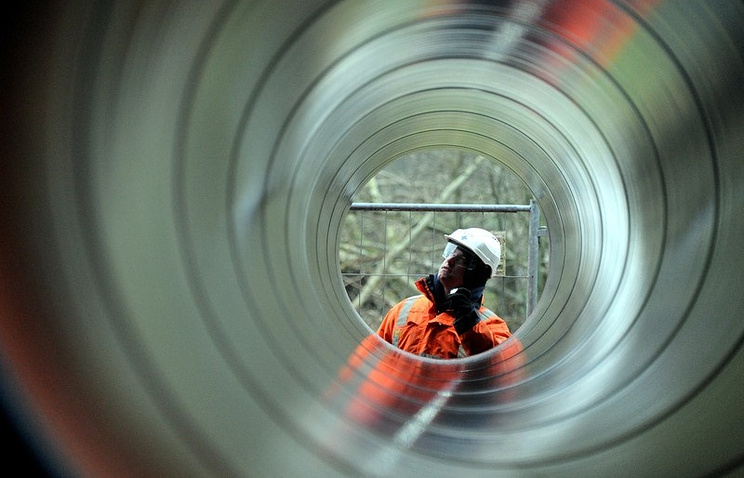 A worker stands behind pipes for a new natural gas pipeline