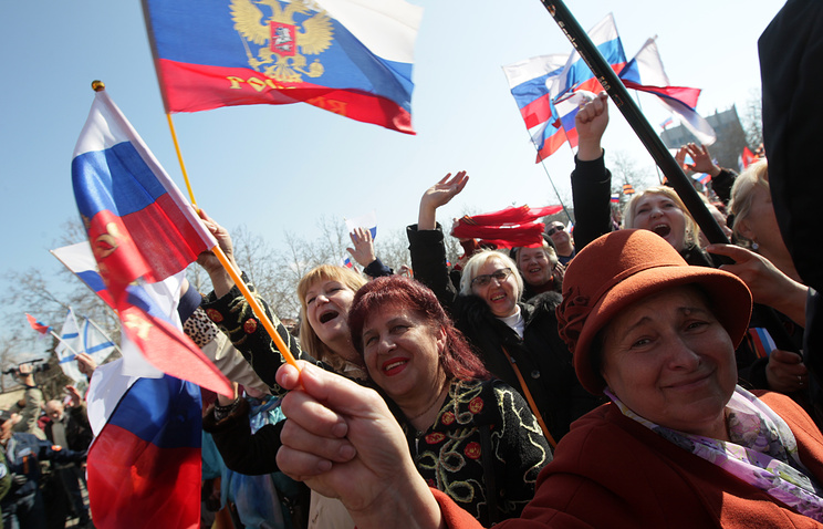 People react as they watch the speech of Russian President Vladimir Putin on a screen in central Sevastopol, Crimea