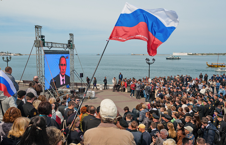 Crimean people watch a TV broadcast with Russian President Vladimir Putin