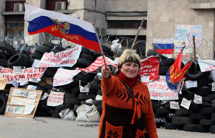A woman waves a Russian flag in Ukraine's Donetsk