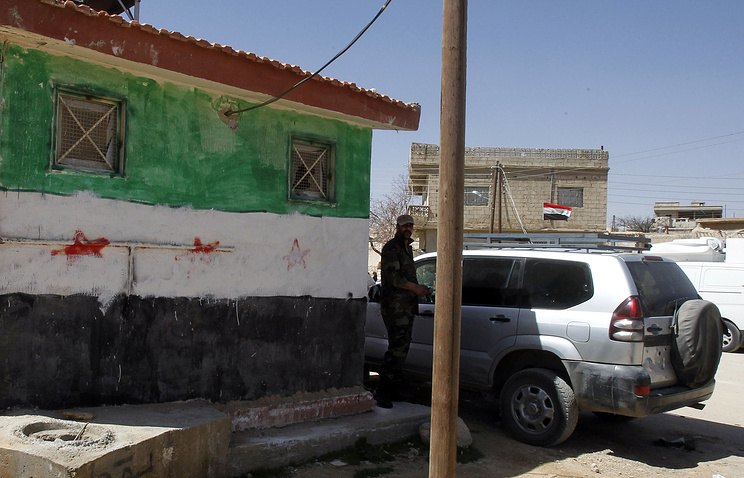A soldier from the Syrian army stands near an office that was under the control of armed groups