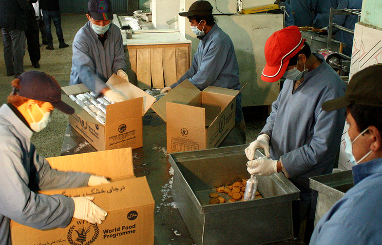 Workers pack biscuits to be donation by the World Food Program