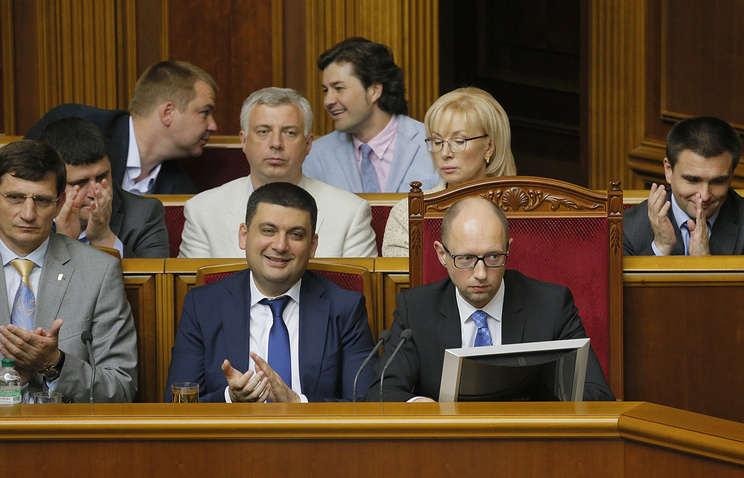 Ukrainian lawmakers and government members applaud after parliament didn't accept Prime Minister Arseniy Yatsenyuk's (front, R) resignation during an emergency session of Ukrainian Parliament in Kiev, Ukraine, 31 July 2014