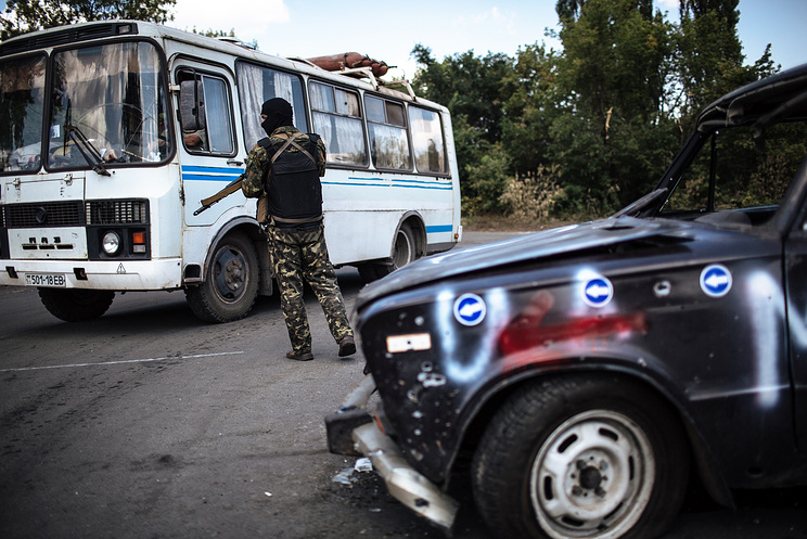 An Ukrainian soldier checks a bus at a checkpoint near city of Donetsk