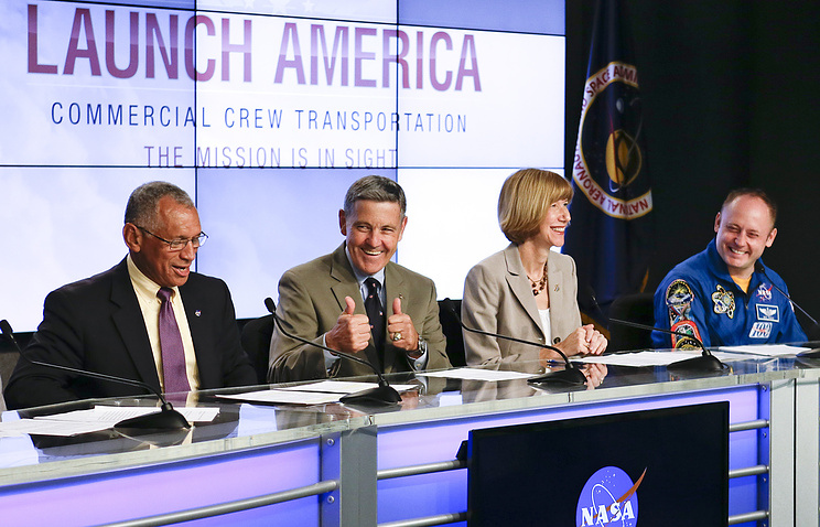 Members of a panel announce NASA's choice of Boeing and SpaceX to ferry astronauts to the International Space Station