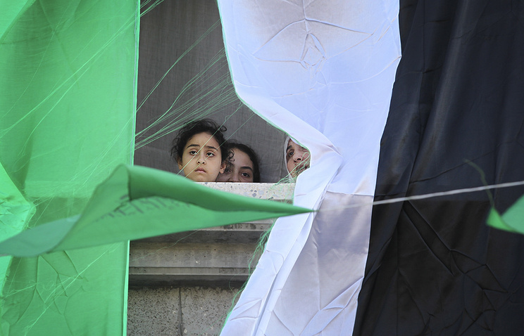 Palestinian girl and a big Palestine flag hanging on the house