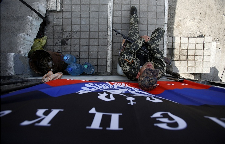 An armed man sits below a flag of the self-proclaimed Donetsk People's Republic