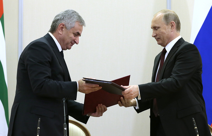 Abkhazian president Raul Khajimba and his Russian counterpart Vladimir Putin exchange documents during a signing ceremony following their meeting on November 24